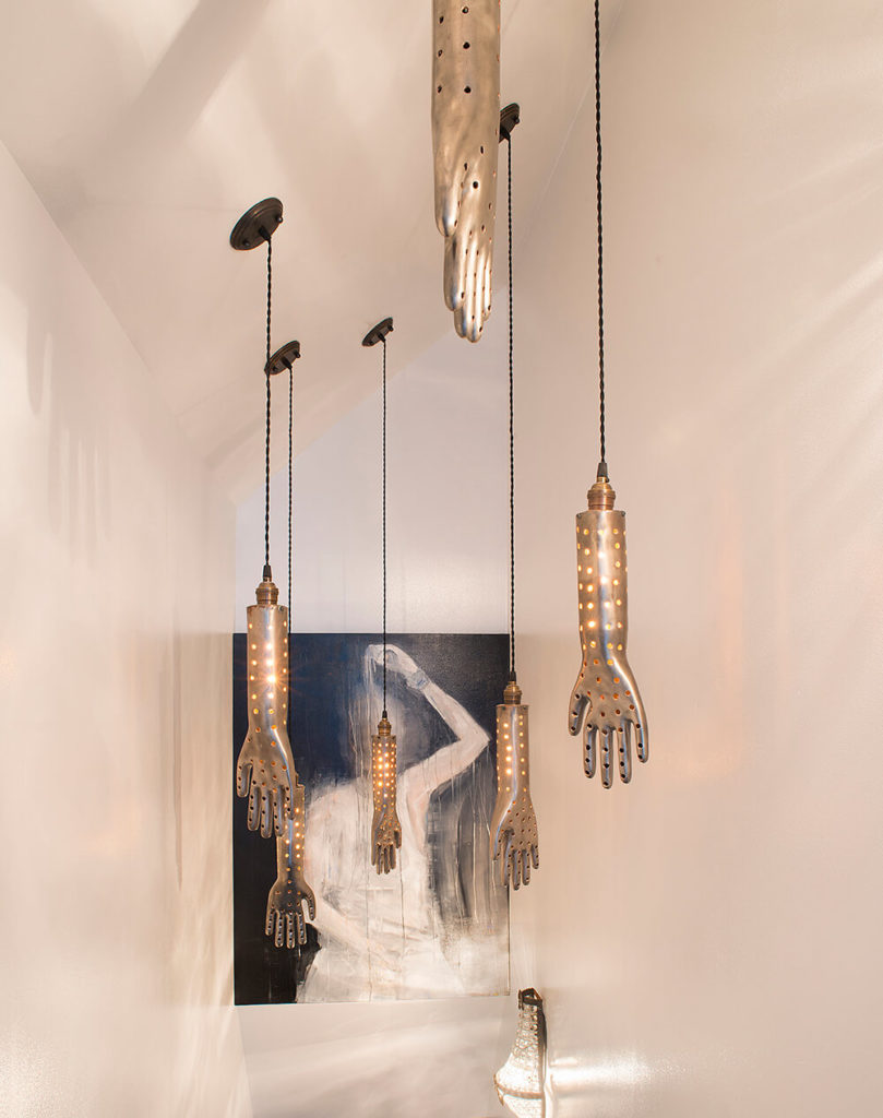 Here's a great example of the eclectic style informing every aspect of the home. The pendant lighting here is a set of perforated steel hands, reaching down from the ceiling.
