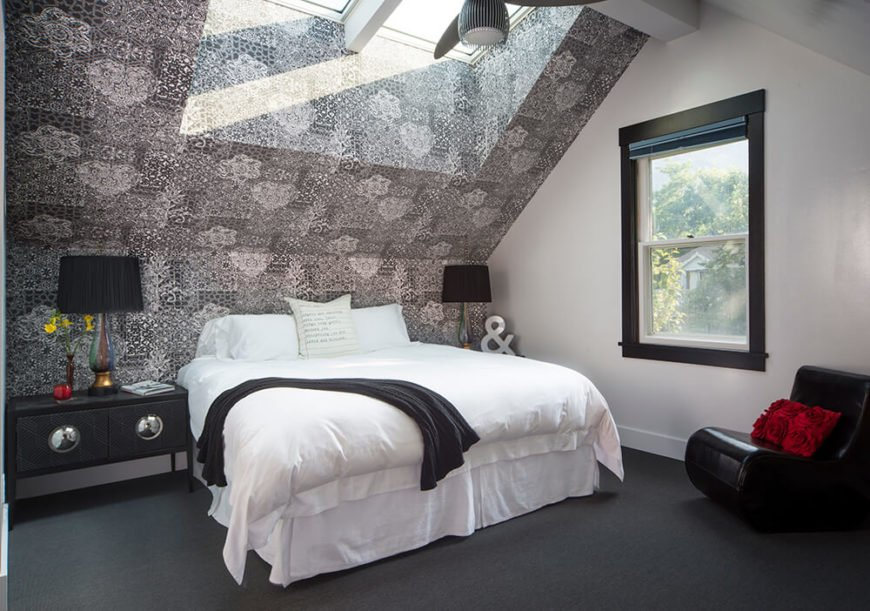 The primary bath enjoys a vaulted ceiling with large skylight, filling the greyscale space with natural light. A single large window looms above the curved black leather accent chair.