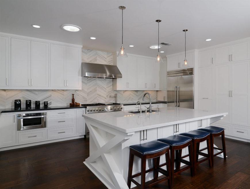 Large kitchen with hardwood floors and white cabinetry along with stylish backsplash and smart appliances.