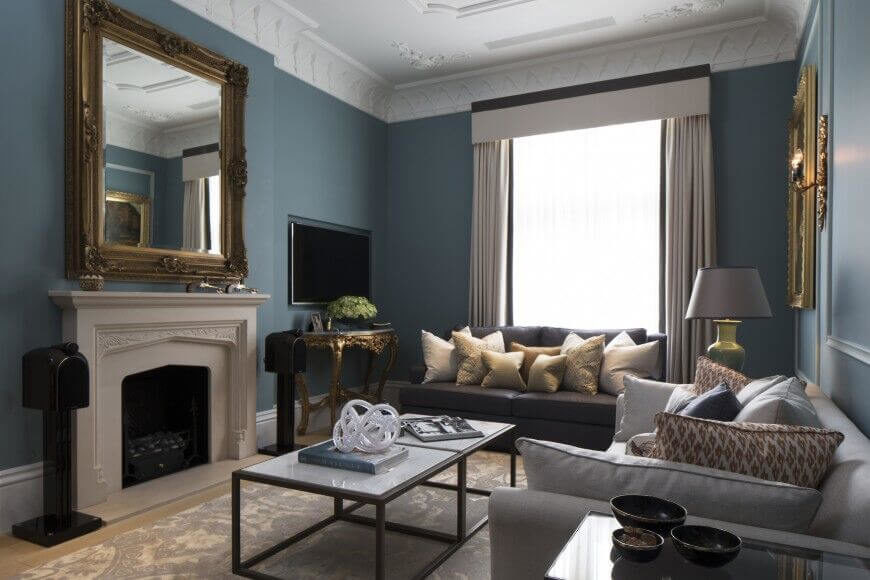 An elegant living room with a few contemporary details, including a glass sculpture on the coffee table and the dusky teal paint color. Gilded mirrors hang above the fireplace mantle and above the contemporary sofa in gray.