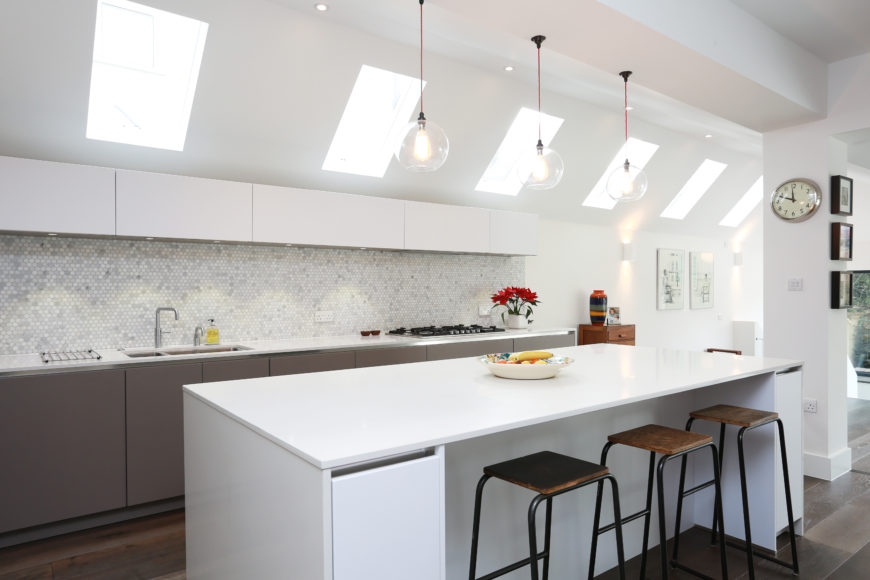 Modern kitchen with white walls and center island along with tiles backsplash and a breakfast bar space lighted by pendant lights.