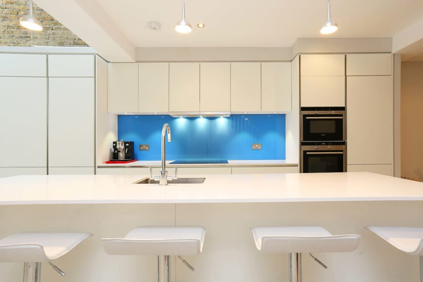 Bright kitchen with a cool backsplash and large center island with smooth white countertop and a space for a breakfast bar.
