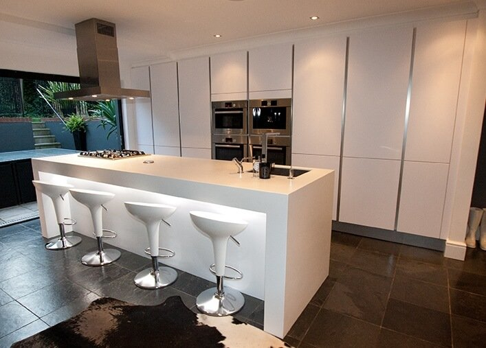 Large single wall kitchen with white cabinetry and smart appliances along with large center island lighted by recessed ceiling lights.