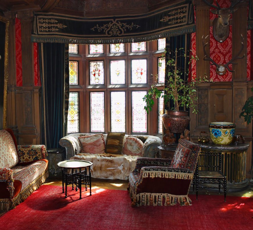 A traditional living room featuring incredible ornate woodwork, tapestries, and heavy drapes complete with tassels. Each piece of furniture is covered in an antique fabric, and are accompanied by a pair of antique tables. The bay windows are in beautiful stained glass.