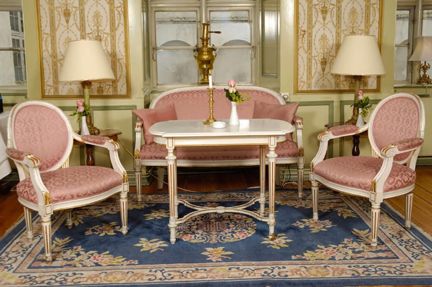 A beautiful, modestly sized living room with a small window nook and white furniture with pink cushions and gilded highlights. Covering the natural hardwood floor is a blue rug with accents of the same pale pink.