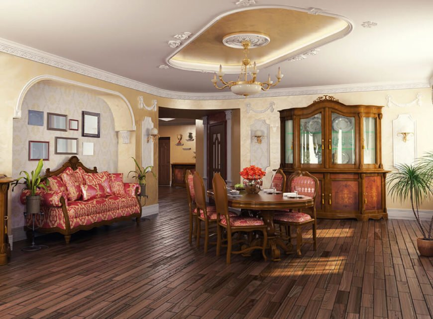 A beautiful, luxurious living room and dining area with wallpaper, a custom tray ceiling with a medallion, and enormous, matching antique furniture. The furniture includes a massive china cabinet, a dining table that seats six, and a large, cushy sofa.