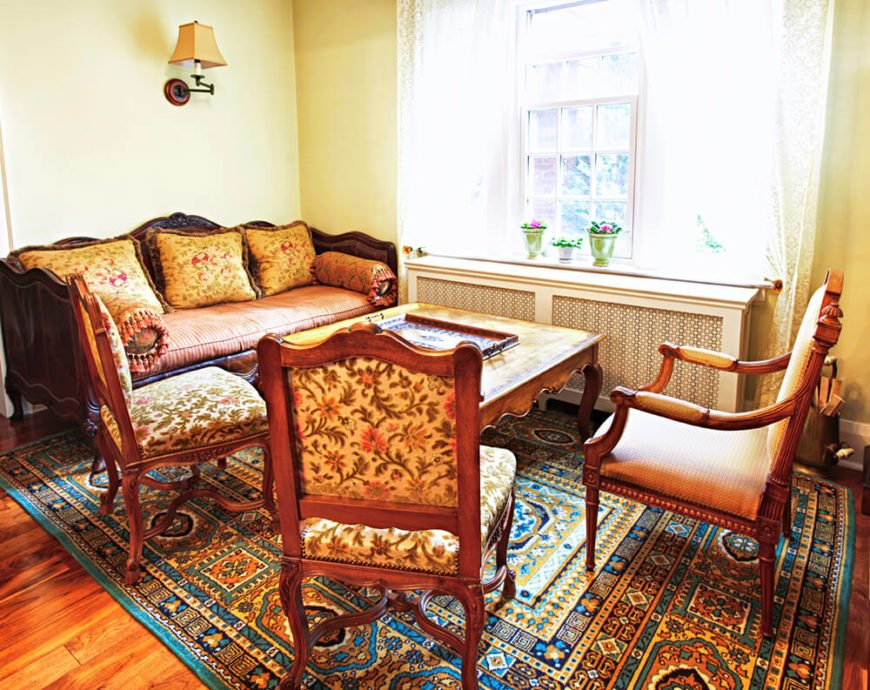 A lovely living room with an armchair, two armless chairs, and a deep sofa with a few throw pillows. The rug covering the hardwood floor has an intricate pattern in yellows, oranges, and blues.