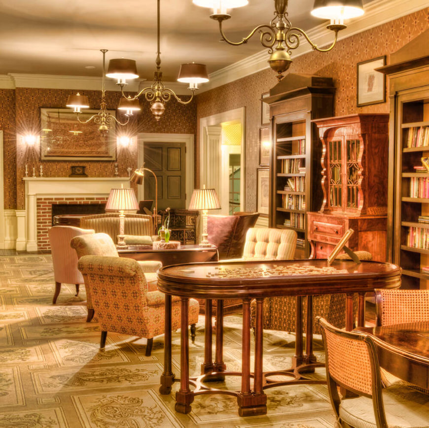 LivingRoomsWithAntiques_08An enormous library with a brick fireplace, built-in bookcases, and a variety of cozy chairs in addition to a large table that houses a puzzle. The patterns of the chairs appear to layer together to give the space the feeling of an old library.