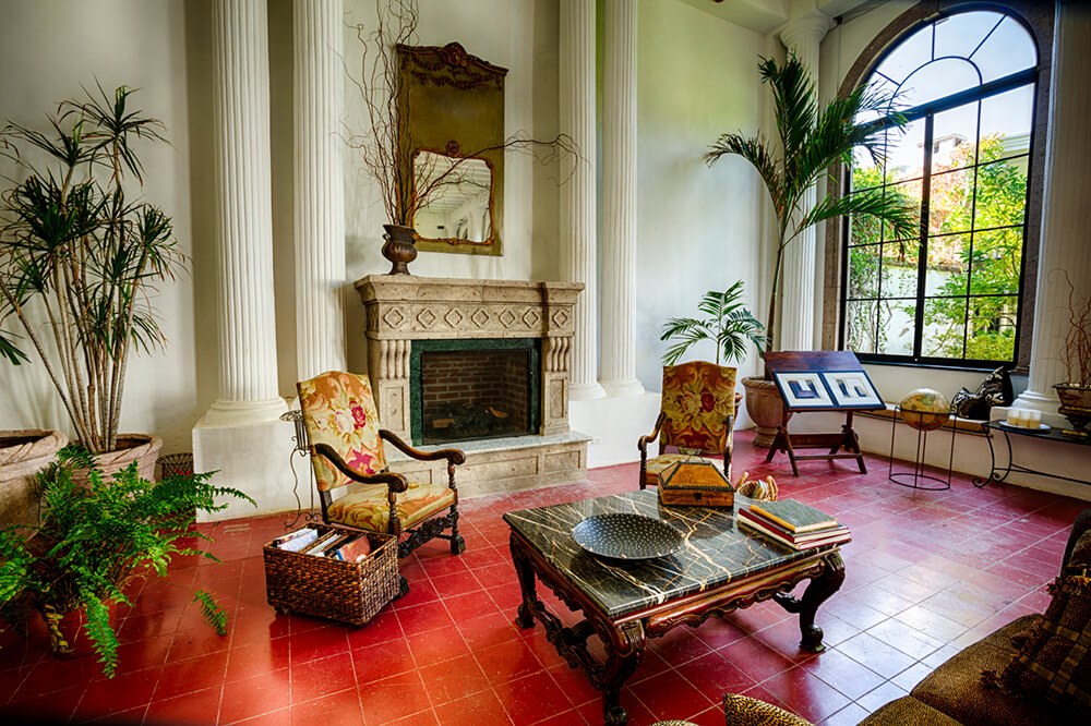A living room with soaring ceilings and a large fireplace. Tall potted plants, like palms, are added to take up some of the space, due to the height of the room. Other furniture includes a marble-topped coffee table, a large sofa, and two antique armchairs in a floral pattern.