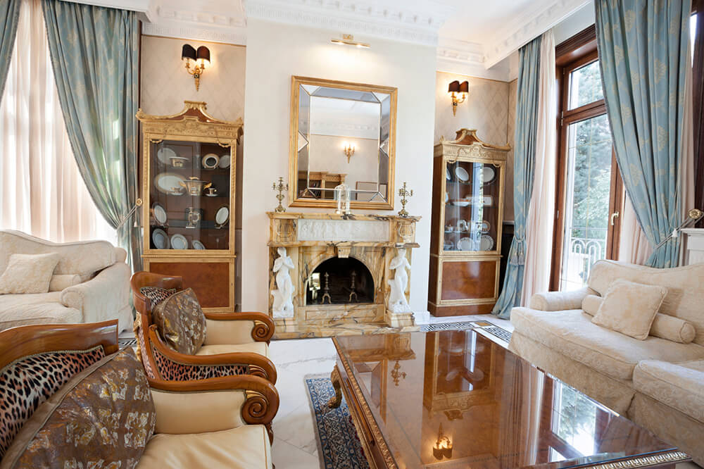 An elegant living room featuring a luxurious marble fireplace complete with statuettes on either side, china cabinets, a glossy coffee table, and a set of matching white sofas, in addition to the armchairs with leopard print accents.