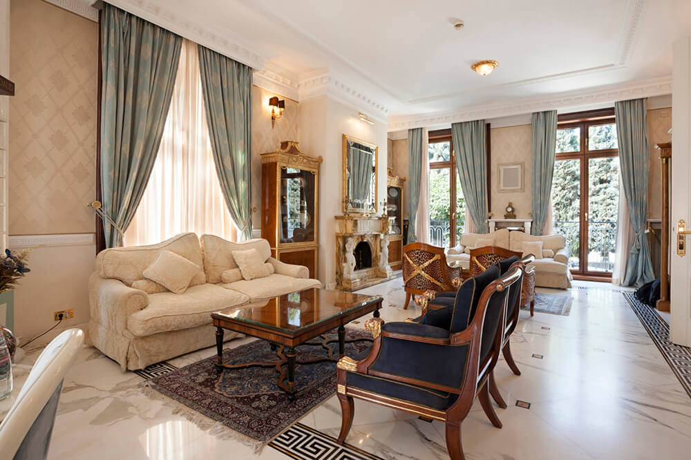 The size of the above living room means that the space has more than enough room for a secondary seating area. From this angle, we can see the second one, which has the matching white sofa and two deep blue armchairs.