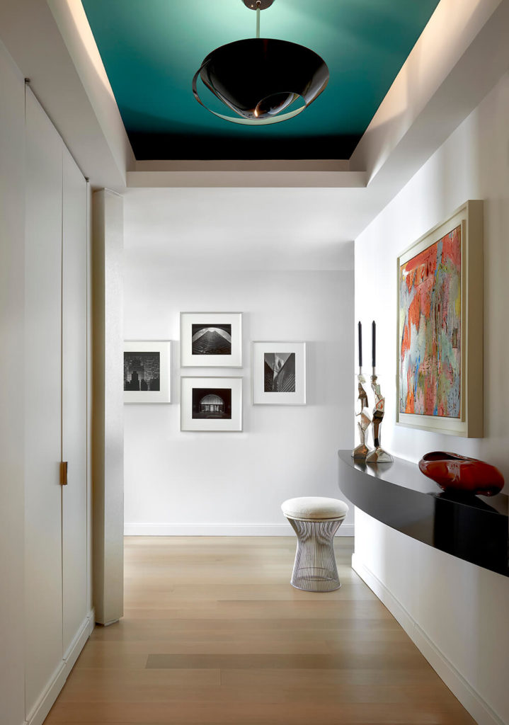 Upon entering the home, we are greeted by the foyer's curved floating shelf topped by a set of ornamental candle holders and a colorful work of art. The light wood flooring and pristine white walls allow the colorful accents to take center stage.