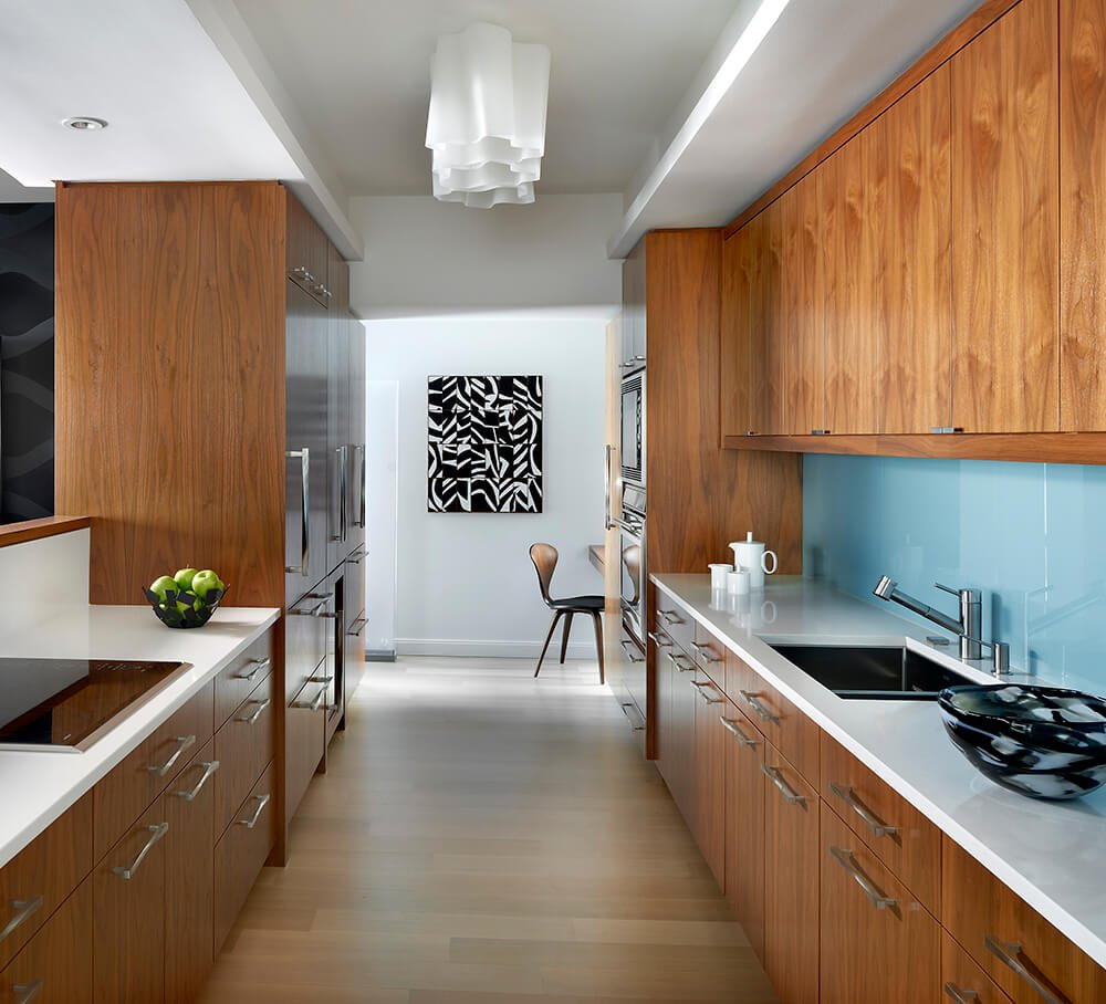 This galley kitchen with walnut finished cabinetry and counters look perfect together with the white countertops, hardwood floors and white walls with artistic decor.