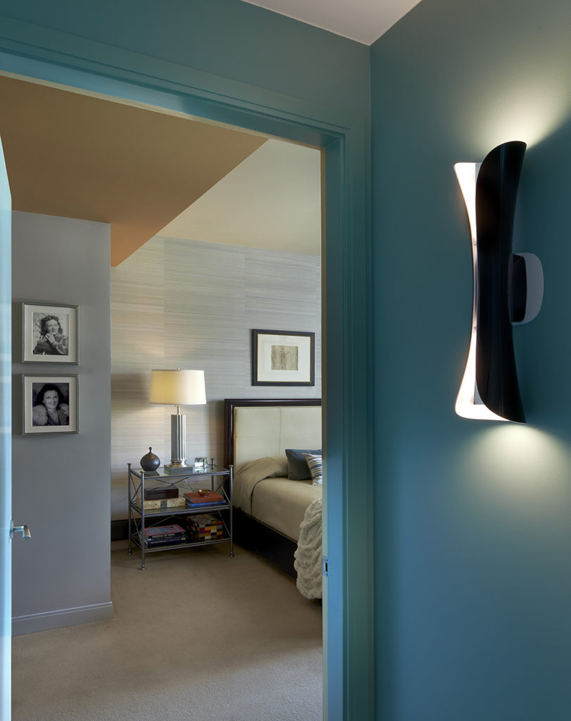 On the other side of the condominium, a Tiffany Blue hallway leads to the more private areas of the home, namely the bedrooms. From the hallway near a curved, modern sconce, we peek into the primary bedroom.