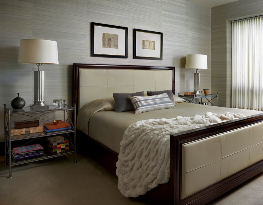 The primary bedroom features a blue-gray silken wall covering that adds substantial texture to the room, in addition to a fluffy blanket, leather panels on the bed frame, and sheer curtains. A light color pallet is soothing, perfect for a bedroom.