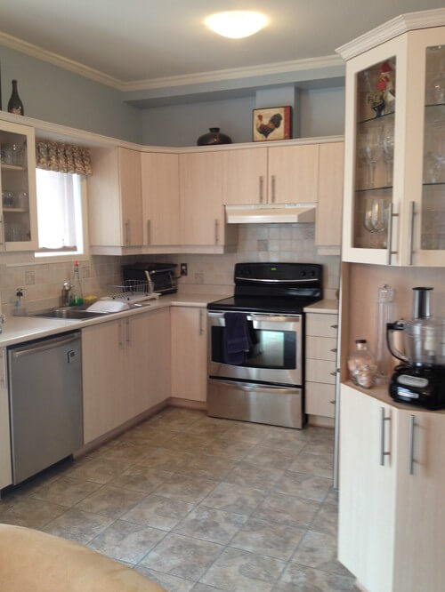 Small kitchen with wooden cabinetry and stainless steel appliances along with tiles backsplash and flooring.