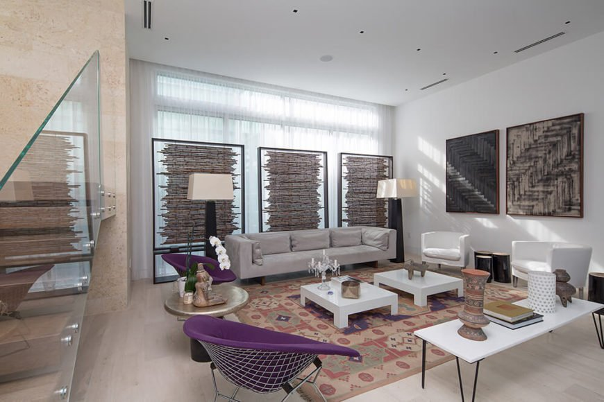 In the spacious living room, bold plum-colored circle chairs add color to a light color pallet. The windows that would expose the room to the street are obscured by sheer white panels, then more effectively by wattle screens behind the modern sofa.