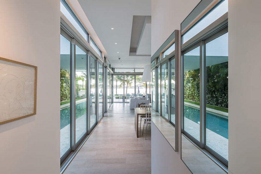 Back on the first floor, the hall stretches into a glass-wrapped dining area and family room. As we enter the larger room, mirrors on the right wall open up the narrow space.