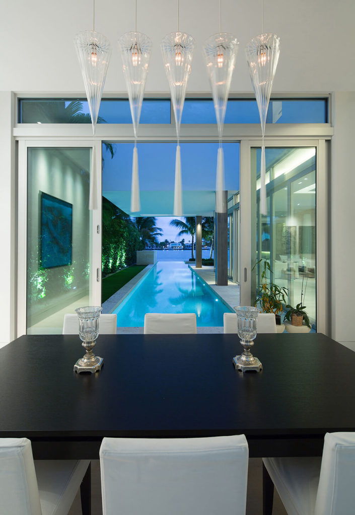 Continuing into the dining room, the rich matte black table is surrounded by upholstered white dining chairs and french doors look out onto the expanse of the infinity pool and out over the bay