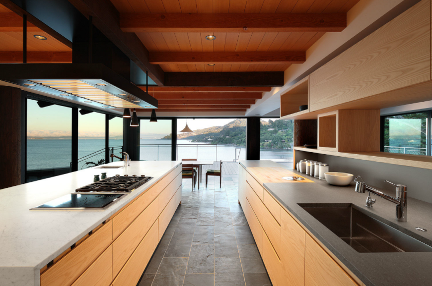 Galley type kitchen with smooth countertops and hardwood cabinetry along with tiles flooring and smart appliances.