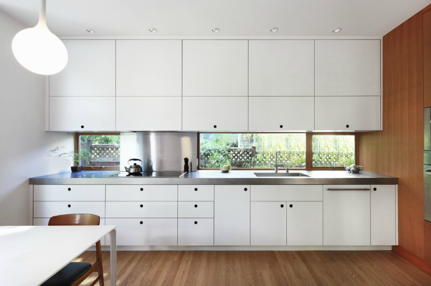 Single wall kitchen with white cabinetry and walls along with granite countertop.