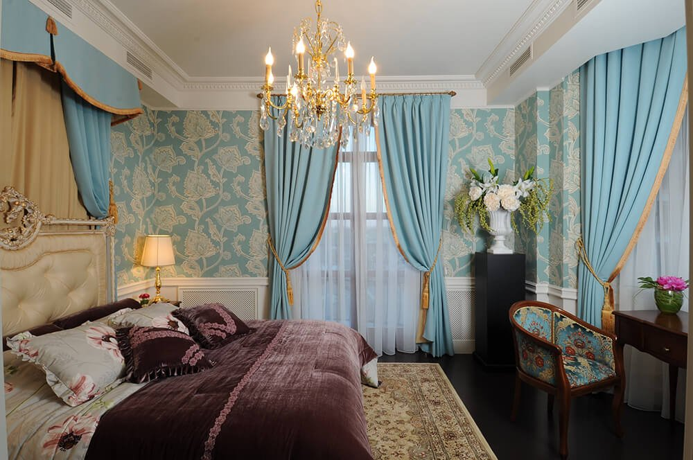 Charming primary bedroom clad in lovely blue floral wallpaper and lighted by a fancy gold chandelier that hung over the cream tufted bed dressed in mauve bedding.