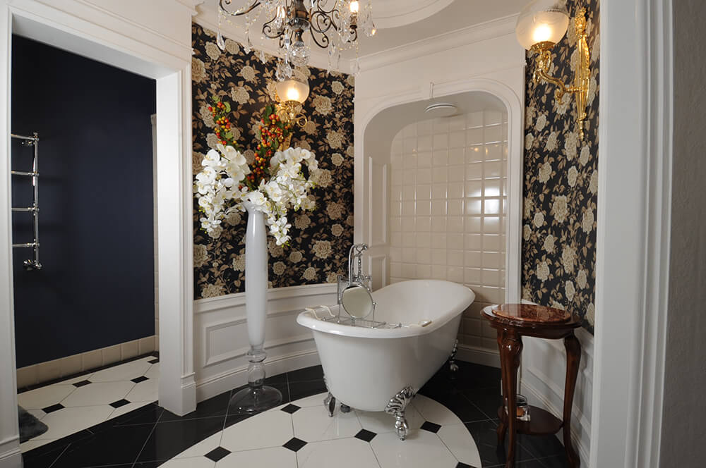 Gorgeous primary bathroom clad in classy floral wallpaper offers a clawfoot bathtub situated in the tiled inset wall. It is accompanied by a tall flower vase and rich wood side table lighted by wall sconces and chandelier.