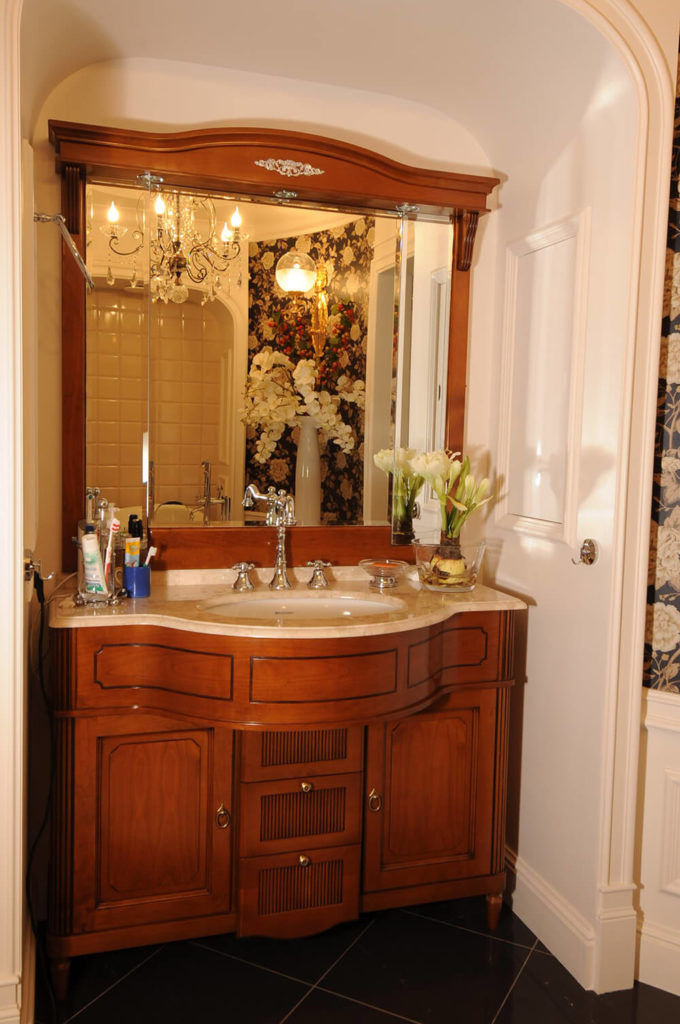 Another bathroom features this ultra-luxurious rich wood vanity with marble countertop. The entire unit is tucked into an arched cove space, conserving the floor plan.