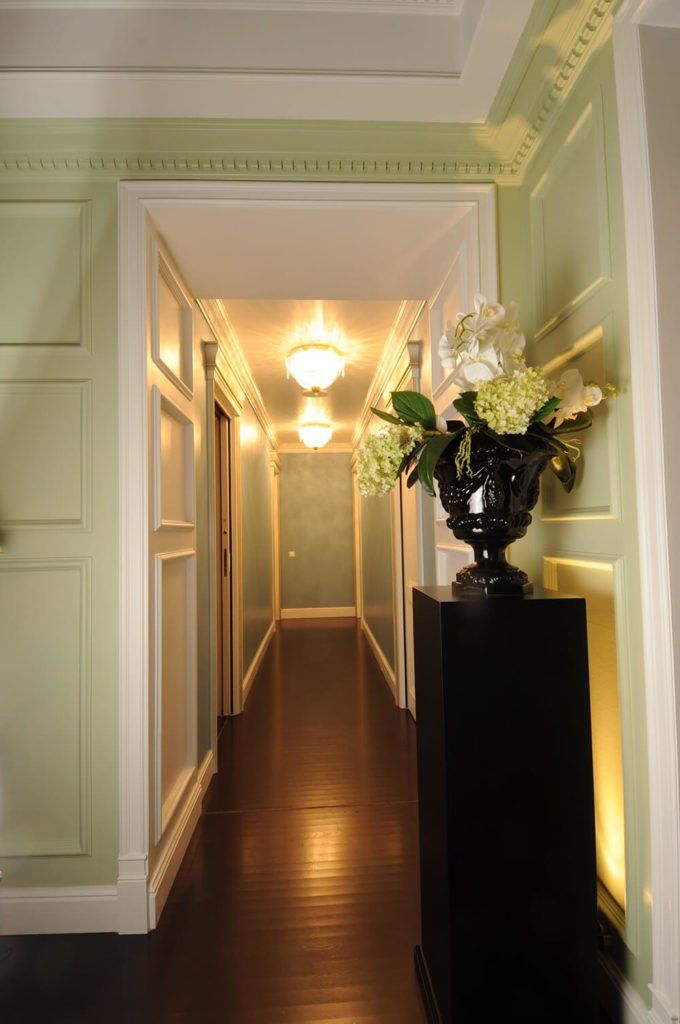 Here's another shot of the lengthy corridors in the home. The rich wainscoting informs nearly every corner of the design, adding a textural contrast with the sleek dark hardwood flooring.