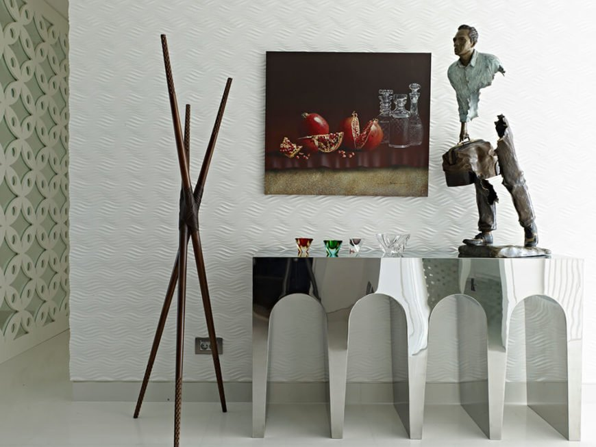 The entryway sees a beautiful chromed Versace console and a sculpture by international artist Bruno Catalano, granting the space a heightened yet well grounded feel.
