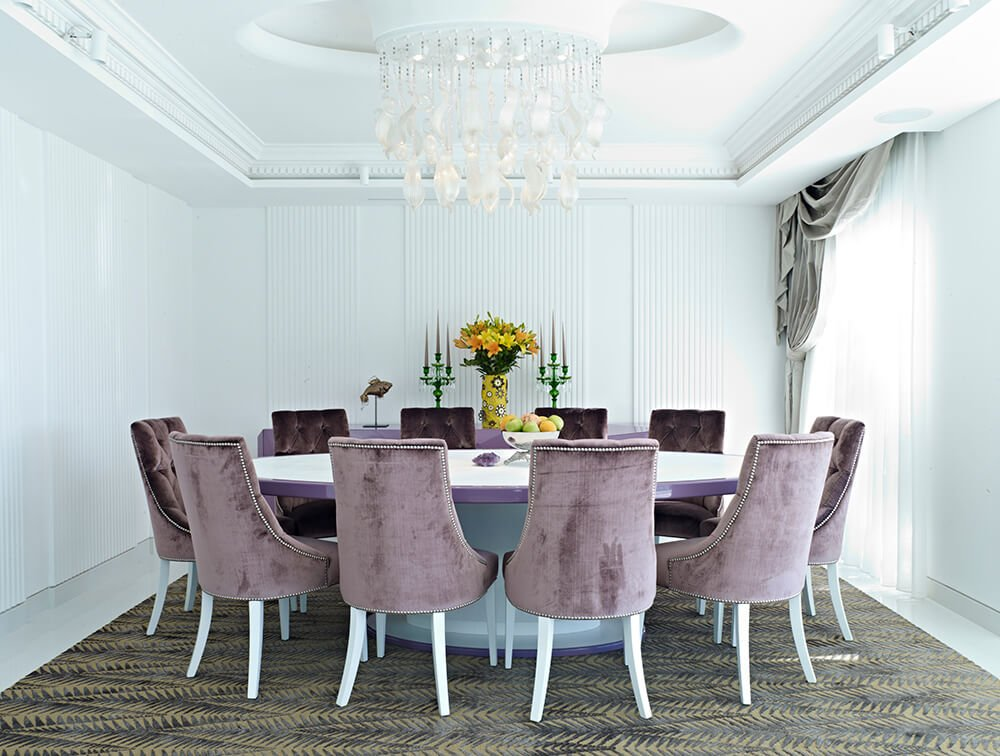A large round dining table set on top of the dining room's carpet flooring and surrounded by white walls and a tray ceiling lighted by a stunning chandelier.