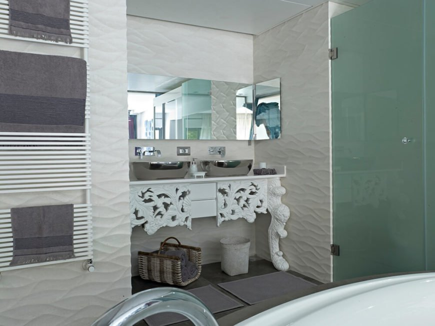 The primary bath is, naturally, the most elegant of the three, with a large soaking tub surrounded by textural white walls. The ornate vanity houses a pair of chromed vessel sinks next to a smoked glass shower enclosure.