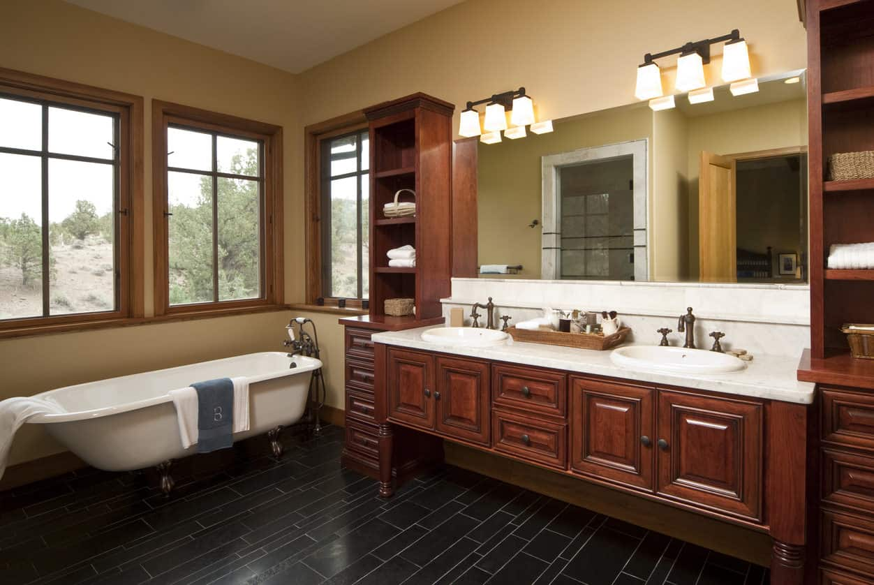 Spacious light-filled primary bathroom with a white clawfoot tub surrounded by windows next to a large built-in double sink vanity.