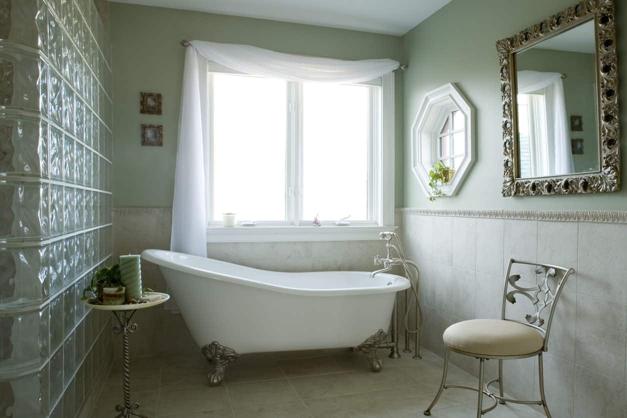 Green master bath with large clawfoot tub alcove area with chair, table and window.