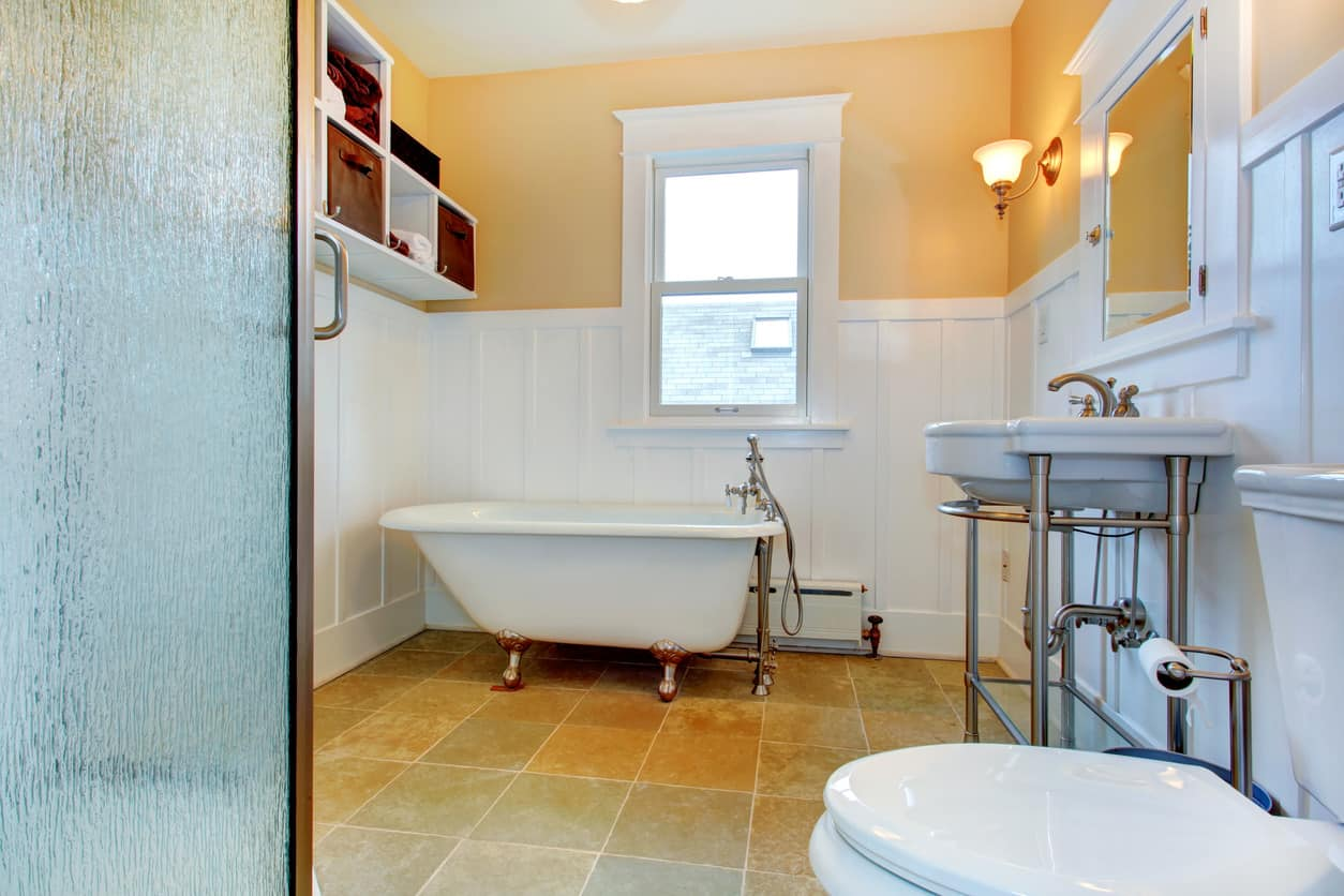 Yellow and white master bathroom with an old clawfoot tub on beige tile floor.