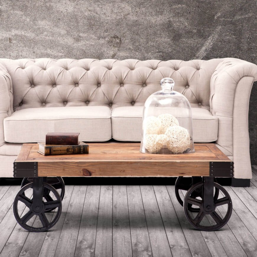 While we've already looked at a couple industrial car style coffee tables, this particular model simply had to be shared as well. Offering a more sleek tabletop construction framed lightly in wrought iron at the corners, it sits on much larger wheels to offer a much taller surface.