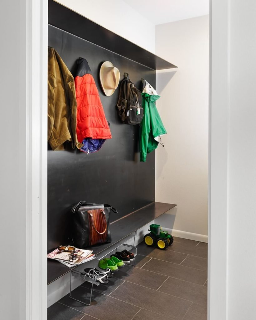 The mudroom features dark tile flooring and a unique metal wall feature, with a built-in shelf. This simple, open place for shoe and coat storage exemplifies the ethos behind the home design.