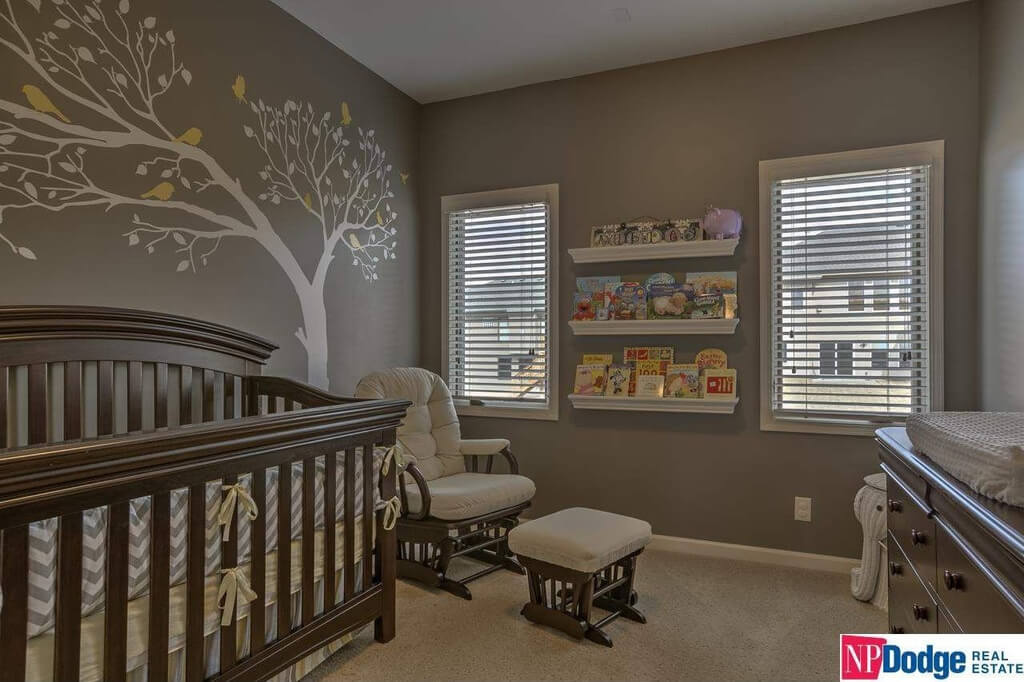 This nursery room features dark finished walls with an interesting tree with birds design along with a carpet flooring.