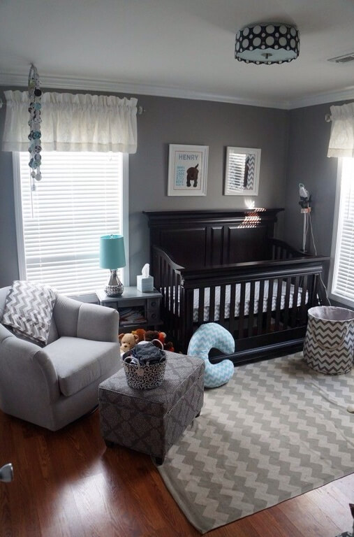 Nursery room with gray walls and black baby bed frame along with a rustic hardwood flooring.