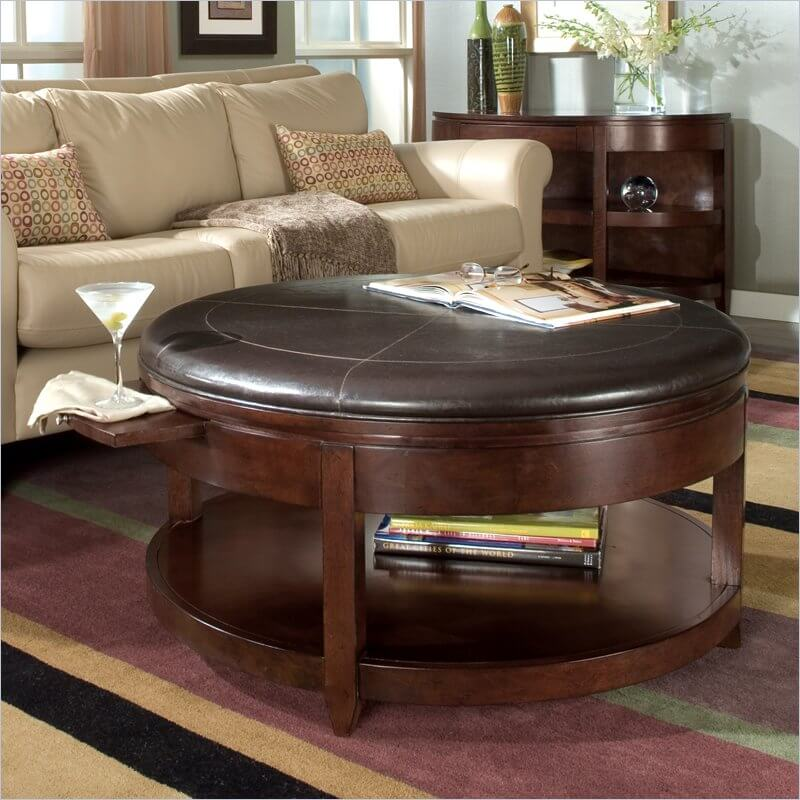 Our first ottoman hybrid is a large circular model with a sleek leather top. The thin cushioning allows for it to be used as a table, while the broad frame makes for plentiful storage space below.