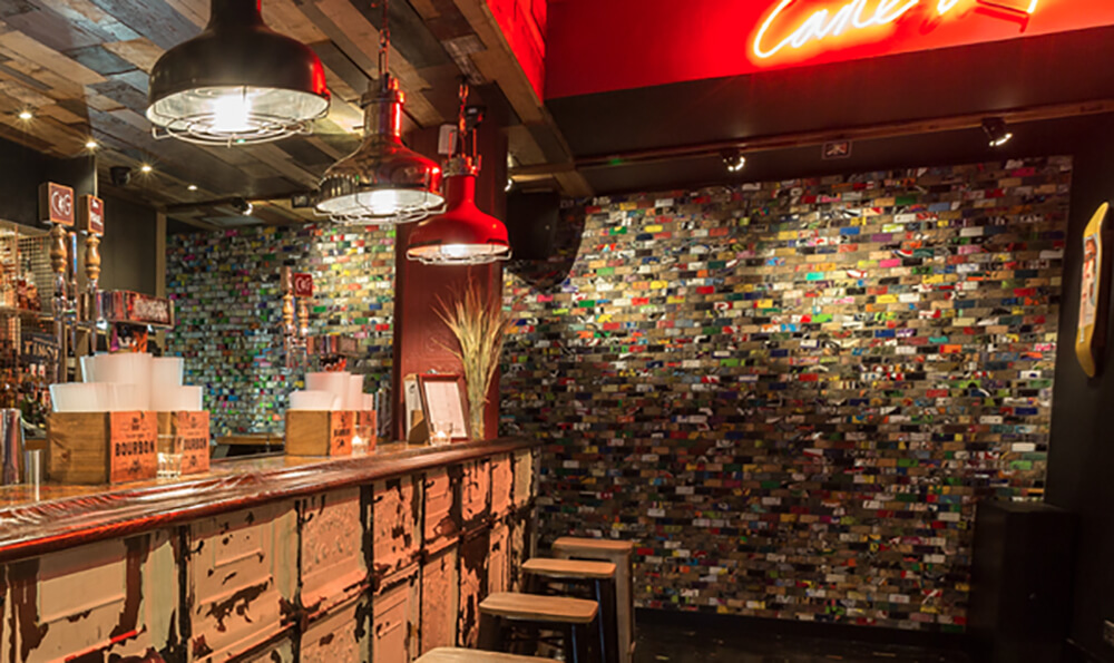 This wall of Board Art will be found in the Cane and Grain Pub in Manchester, England. The whole wall is covered with board art, and it absolutely brings the space to life. The mural of recycled skateboard art not only makes the space feel exciting and lively, it tells a different story with each tile. We can enjoy the wall as a whole, or examine it closely and find a unique piece of art on every tile.