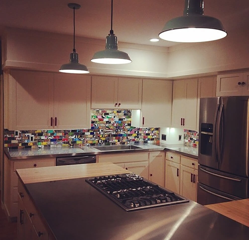 This customer of Art of Boards has a full backsplash installed in their kitchen. The kitchen itself has a traditional design, with chrome surfaces on the island and countertops, as well as on the fridge. The white cabinetry around the backsplash helps to make the Board Art stand out, making it the center of attention in the space.