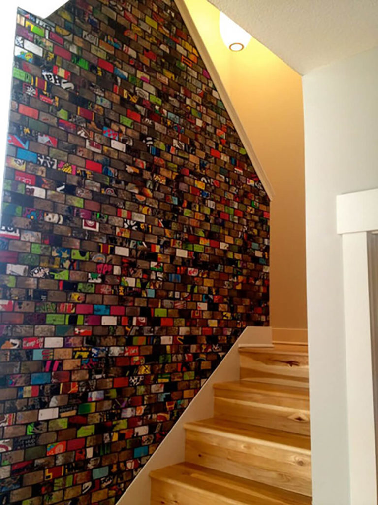 Art of Boards does not limit themselves to just backsplashes and commercial designs! Featured here is a customer's staircase with the board art along the wall. With every unique design, we can see a few different colors and patterns that stick out and kind of set the tone for the whole piece. In this instance, we notice a lot of lime green and red coloring.
