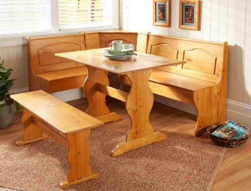 Our first corner dining set appears in rich natural wood, with an unfussy but detailed design. The high seatbacks are carved with a simple design, while the base is organically curvy. This set would work perfectly in a traditional or rustic styled home.