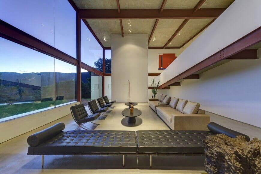 This massive space contains plenty of seating via leather chairs, a long chaise, and a long leather couch. The seating areas are separated by oval shaped coffee tables. The red I-beams and cement poured floor suggests and industrial theme.
