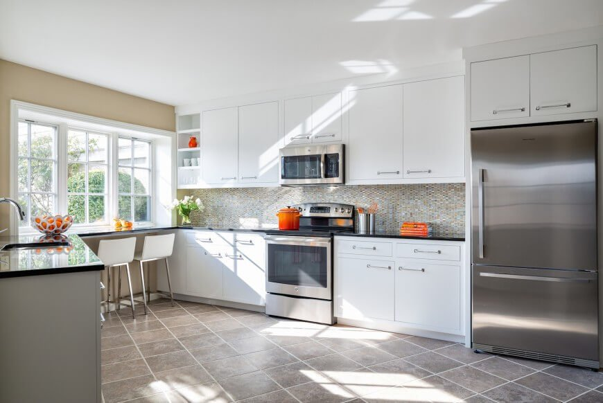 Bright and open design informs this kitchen, flush with white cabinetry and stainless steel appliances. The intricate tile backsplash adds a layer of complexity to the light room, helping diffuse the contrast with the black countertops.