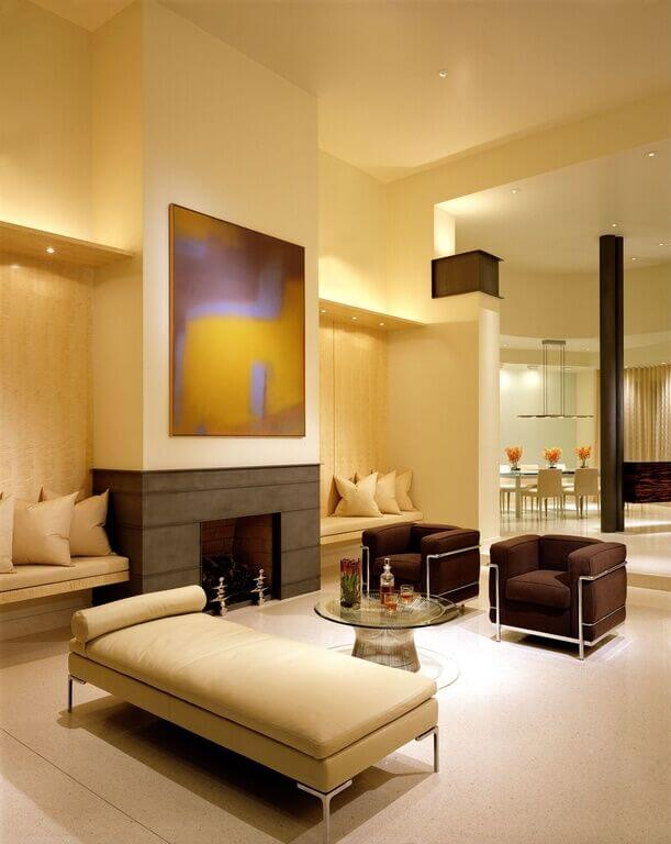 The unique lighting in this living room creates a calming atmosphere, and helps to accent specific areas around the chairs and coffee table. The large fireplace is located just beneath a large piece of artwork, with recessed sections on either side of the fireplace, providing more seating.