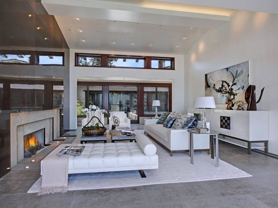 A large, open living room, this space is well lit by both natural and artificial lighting. The fireplace is centered in the wall, and surrounded by a sleek reflective finish. The furniture is all white and sits upon a large white area rug.