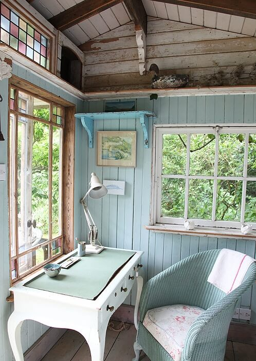 This work space is small, but kept bright with light colors and plenty of windows letting in natural light. The desk sits directly beneath a large window with stained glass corners. These subtle accents help to give this space it's unique character.
