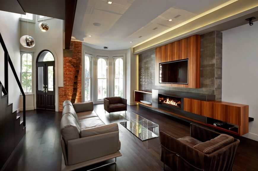 Brick walls don't always dominate a room. In this example, the sliver of brick near the front door mixes nicely with the more modern looking elements, including the polished brick and wood floors.